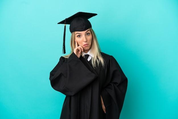 若い大学は、アイデアを考えて孤立した青い背景の上に卒業します