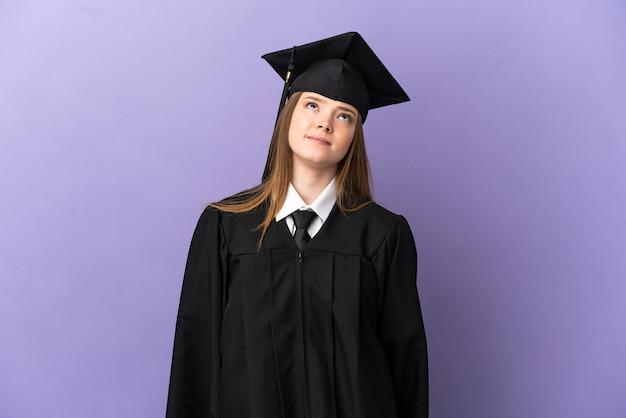 Молодой выпускник университета на изолированном фиолетовом фоне и смотрит вверх