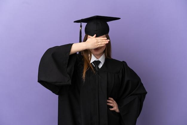 Молодой выпускник университета на изолированном фиолетовом фоне, закрывая глаза руками. не хочу что-то видеть