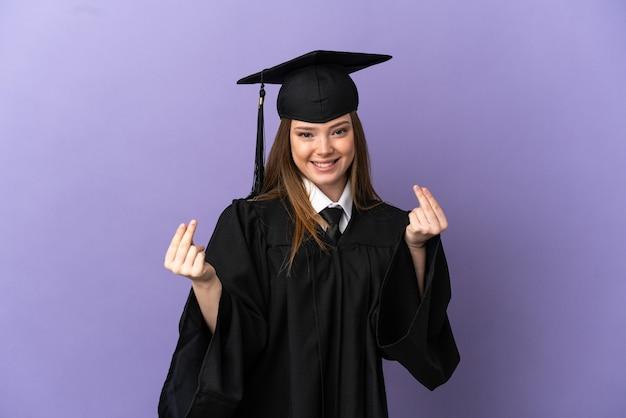 돈 제스처를 만드는 고립 된 보라색 배경 위에 젊은 대학 졸업