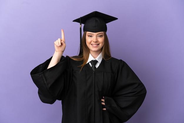 Молодой выпускник университета на изолированном фиолетовом фоне, указывая на отличную идею