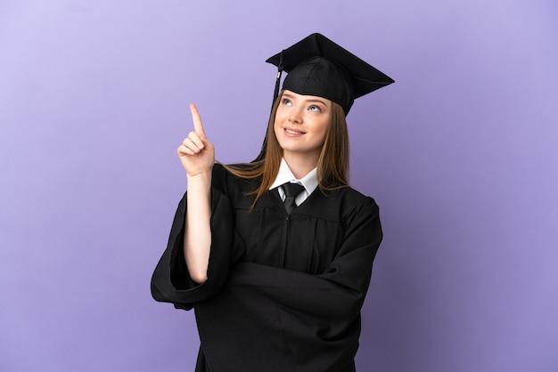 若い大学は素晴らしいアイデアを指している孤立した紫色の背景の上に卒業します