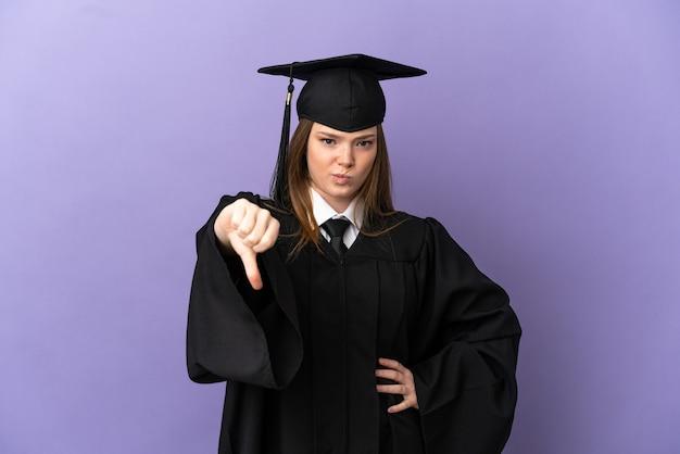 Молодой выпускник университета на изолированном фиолетовом фоне показывает большой палец вниз с негативным выражением лица