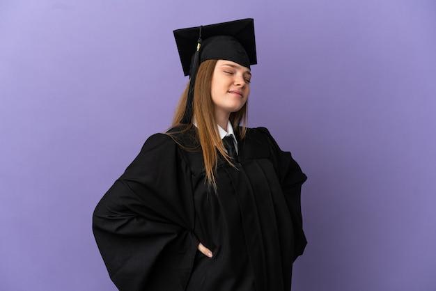 Молодой выпускник университета на изолированном фиолетовом фоне страдает от боли в спине из-за того, что приложил усилия Premium Фотографии