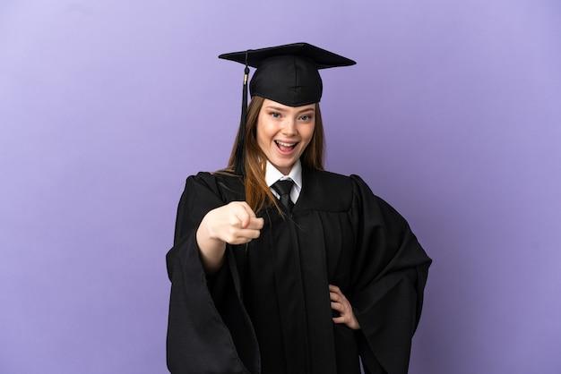 若い大学卒業生は、孤立した紫色の背景に驚いて正面を向いています