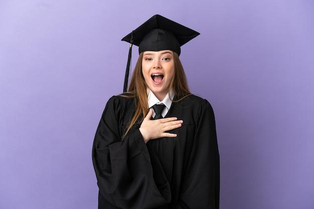 孤立した紫色の背景の上に若い大学卒業生は、右を見ながら驚いてショックを受けました