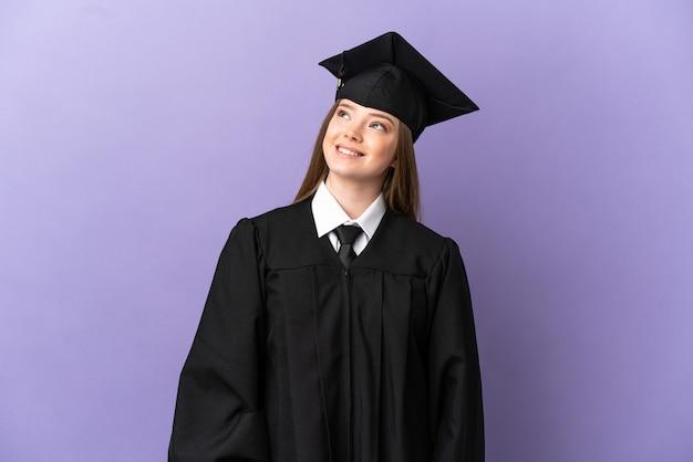 Молодой выпускник университета на изолированном фиолетовом фоне думает о идее, глядя вверх