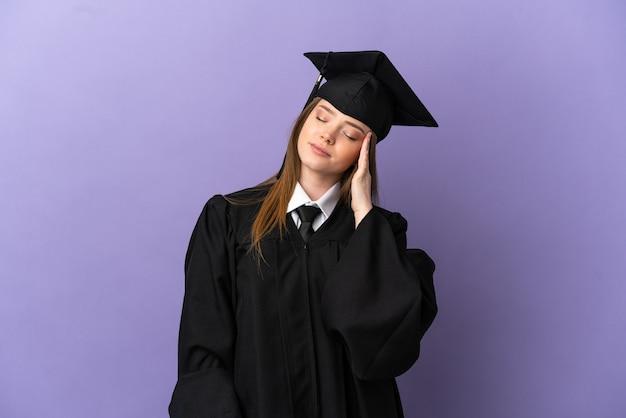 두통으로 고립 된 보라색 배경 위에 젊은 대학 졸업