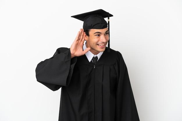 Молодой выпускник университета на изолированном белом фоне слушает что-то, положив руку на ухо