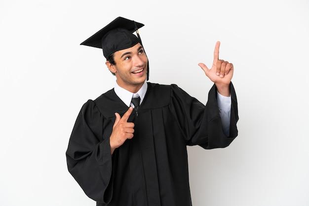Молодой выпускник университета на изолированном белом фоне, указывая указательным пальцем на отличную идею