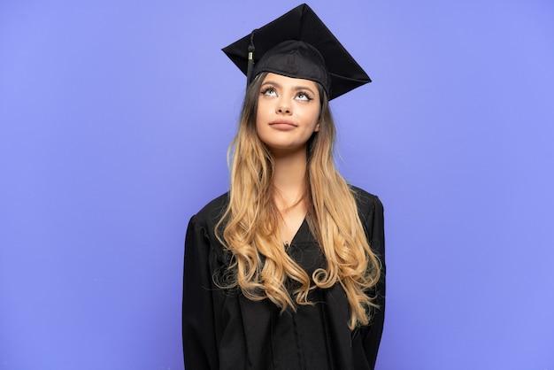 若い大学卒業生ロシアの女の子が白い背景で隔離され、見上げる