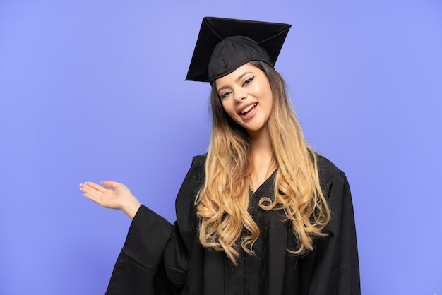 흰색 배경에 격리된 젊은 대학 졸업 러시아 소녀가 초대하기 위해 손을 옆으로 내밀었습니다.