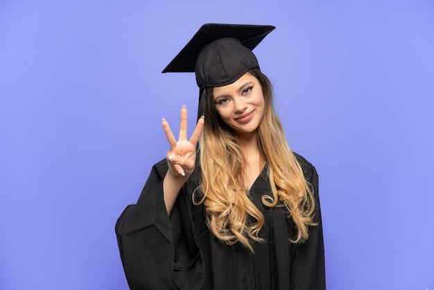 Молодая русская девушка выпускник университета изолирована на белом фоне счастлива и считает три пальцами