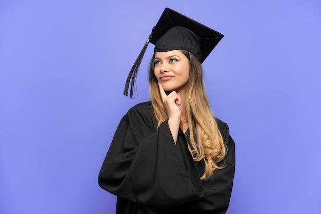 Молодая русская девушка с выпускником университета изолирована на белом фоне, сомневаясь, глядя вверх