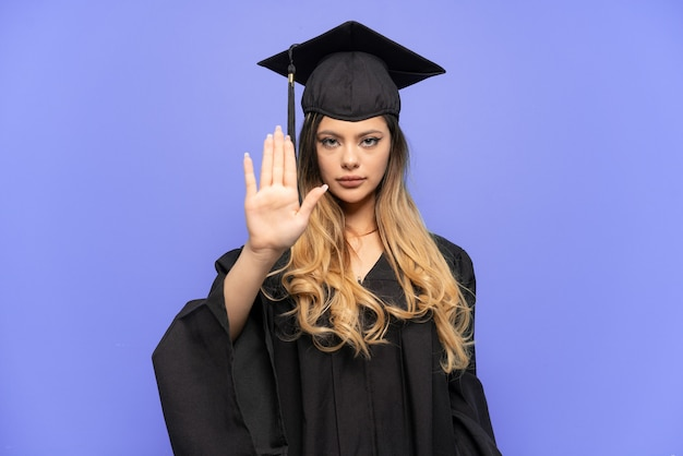 停止ジェスチャーを作る白い背景で隔離の若い大学卒業生ロシアの女の子