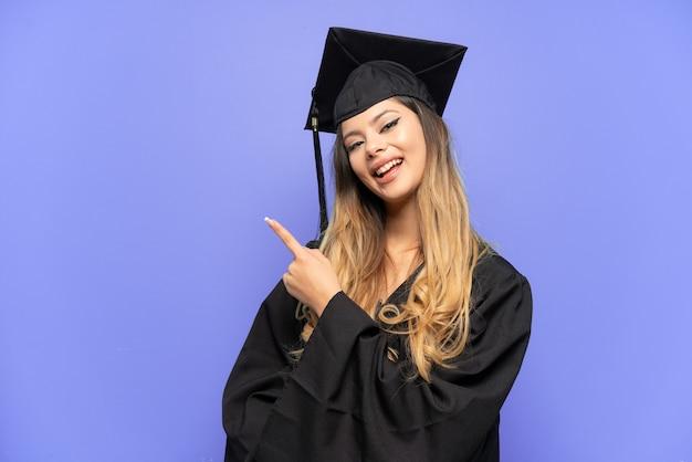 製品を提示する側を指している白い背景で隔離の若い大学卒業生ロシアの女の子