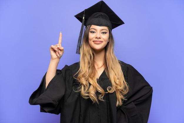 좋은 아이디어를 가리키는 흰색 배경에 고립 된 젊은 대학 졸업 러시아 소녀