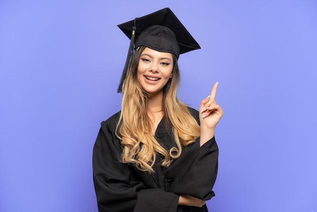 흰색 배경에 격리된 젊은 대학 졸업 러시아 소녀는 최고의 표시로 손가락을 들고 들어올립니다.