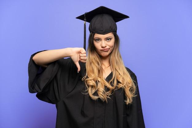 젊은 대학 졸업 러시아 소녀 부정적인 표정으로 아래로 엄지손가락을 보여주는 흰색 배경에 고립