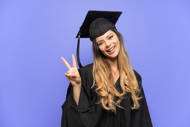 笑顔と勝利のサインを示す白い背景で隔離の若い大学卒業生ロシアの女の子