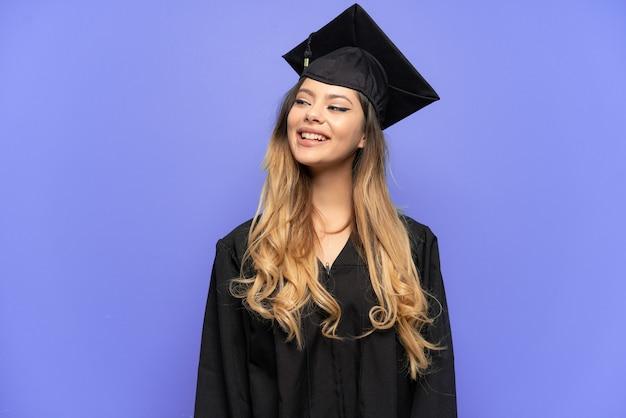 見上げながらアイデアを考えて白い背景で隔離の若い大学卒業生ロシアの女の子