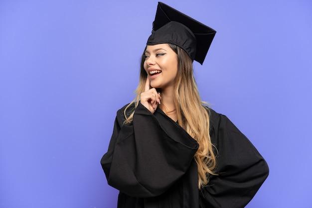 Молодая русская девушка-выпускник университета изолирована на белом фоне, думая об идее, глядя вверх