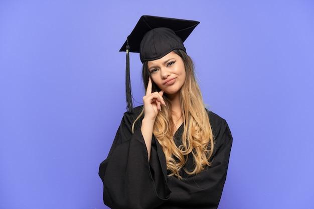 아이디어를 생각 하는 흰색 배경에 고립 된 젊은 대학 졸업 러시아 소녀