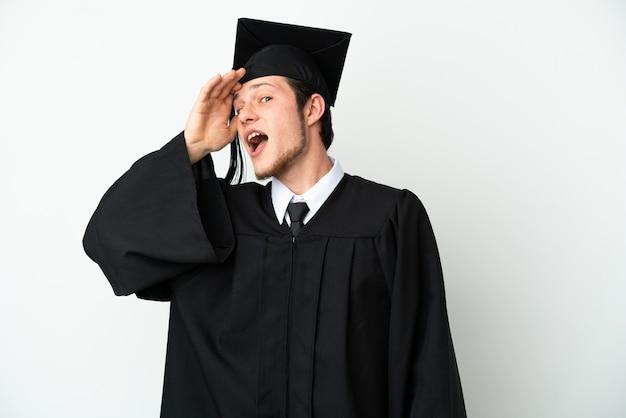 Молодой российский выпускник университета изолирован на белом фоне делает неожиданный жест, глядя в сторону