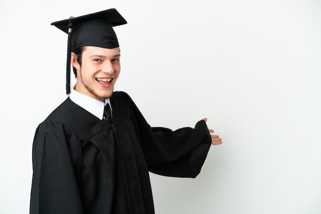 Молодой российский выпускник университета изолирован на белом фоне, протягивая руки в сторону для приглашения приехать