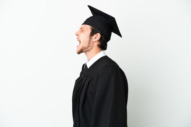 Молодой российский выпускник университета, изолированные на белом фоне, смеясь в боковом положении