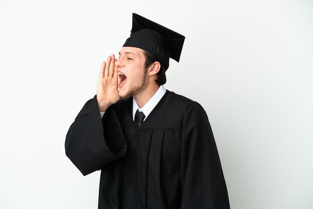 Молодой российский выпускник университета изолирован на белом фоне кричит с широко открытым ртом в сторону