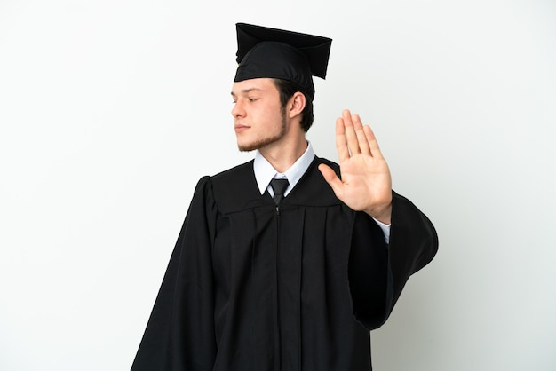 Young university russian graduate isolated on white background making stop gesture and disappointed