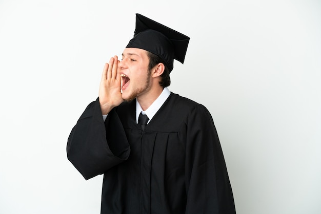 Young university russian graduate isolated on white background shouting with mouth wide open to the side