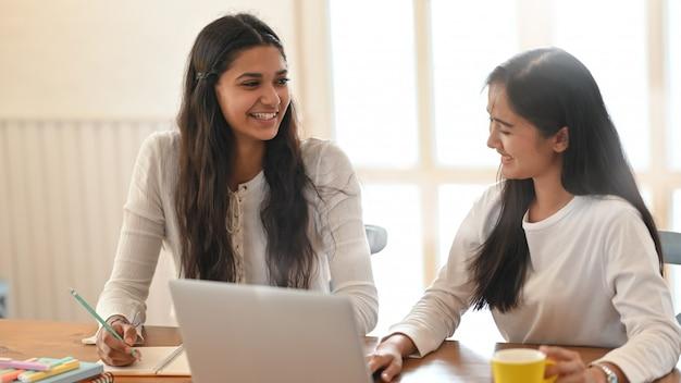若い大学生が快適なリビングルームの上の木製のワーキングデスクで一緒に座っているときにコンピューターのラップトップを使用して彼らのレッスンを指導