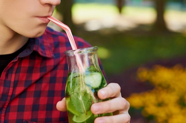 認識できない若い男は、緑豊かな公園の背景にジュースと健康的なデトックス茶を飲みます。スーパーフード、健康、夏の鮮度、ベジタリアンフードのコンセプト