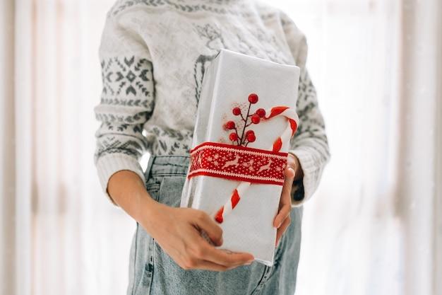 認識できない若い女性は、赤いひもとキャンディーと金属紙のギフトボックスに保持します