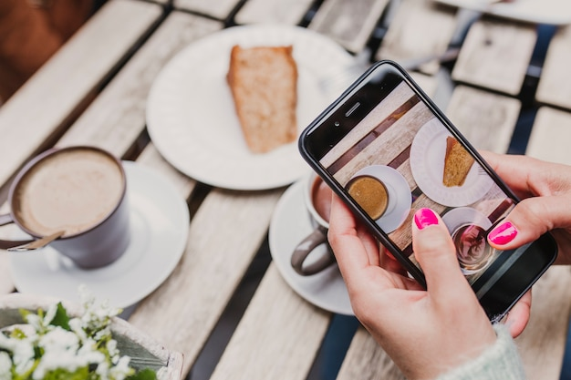 Young unrecognizable woman taking a picture with mobile phone of her breakfast, a cup of coffee and a piece of cake. breakfast concept