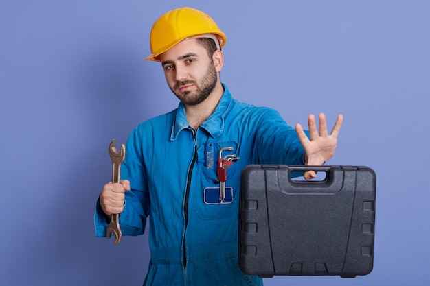 Young unshaved male with wrench and tool case in hands, guy wearing helmet and overalls, looking directly at camera