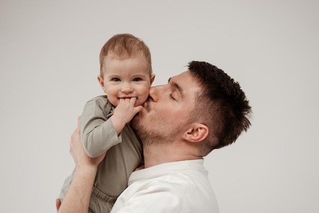 Молодой небритый отец целует свою маленькую дочку в щеку, ребенок улыбается, глядя в камеру и держа три пальца во рту