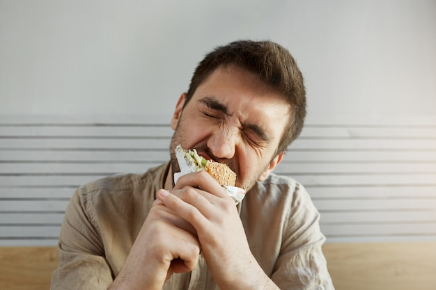 Young unshaven handsome guy with dark hair eating sandwich in fast food with closed eyes, with happy and satisfied expression.
