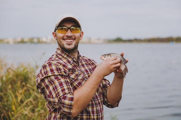 체크무늬 셔츠, 모자, 선글라스를 끼고 면도를 하지 않은 채 웃고 있는 젊고 행복한 남자는 물고기를 잡고 팔에 안고 물 배경에 있는 호수 기슭에서 기뻐합니다. 라이프 스타일, 어부의 레저 개념