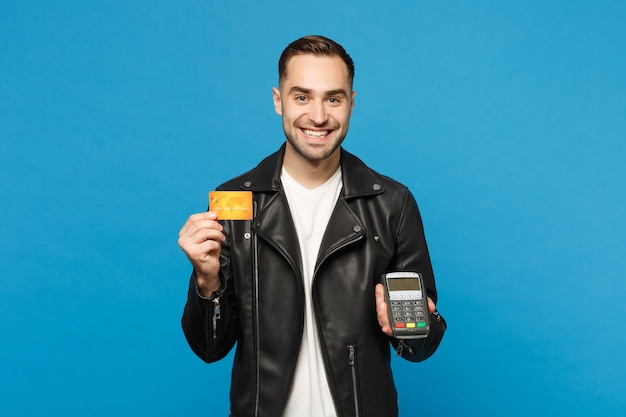 Young unshaven man black jacket white t-shirt hold in hand wireless modern bank payment terminal to process and acquire credit card payments isolated on blue wall background. people lifestyle concept.