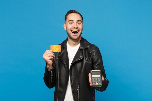 若い無精ひげを生やした男の黒いジャケット白いtシャツは、青い壁の背景に分離されたクレジットカードの支払いを処理して取得するためにワイヤレスのモダンな銀行決済端末を手に持っています。人々のライフスタイルの概念。