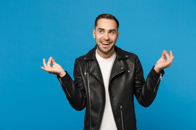 Young unshaven man in black jacket white t-shirt rubbing fingers, showing cash gesture, asking for money isolated on blue wall background studio portrait. people lifestyle concept. mock up copy space.
