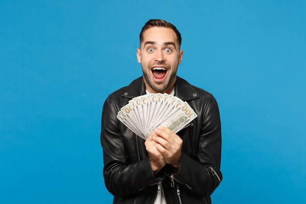 Young unshaven man in black leather jacket white t-shirt holding fan of cash money in dollar banknotes isolated on blue wall background studio portrait. people lifestyle concept. mock up copy space.