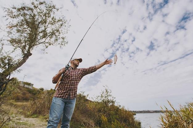 Giovane uomo con la barba lunga in camicia a scacchi, berretto, occhiali da sole tiene la canna da pesca e allunga la mano al pesce pescato sulla riva del lago vicino ad arbusti e canne. stile di vita, ricreazione, concetto di svago del pescatore