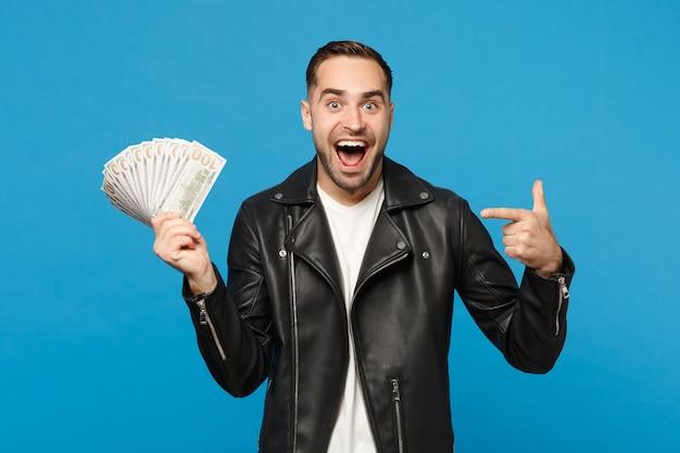 Молодой небритый человек в черной кожаной куртке белой футболке держит веер наличных денег в долларовых банкнотах, изолированных на синем стенном фоне студийного портрета. концепция образа жизни людей. копируйте пространство для копирования.