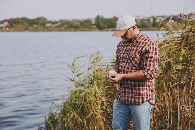 바둑판 무늬 셔츠와 모자를 쓴 면도를 하지 않은 젊은 남자는 작은 상자에서 구더기 미끼를 꺼내 호수, 관목, 갈대를 배경으로 막대에 얹습니다. 라이프 스타일, 어부의 레크리에이션, 레저 개념.