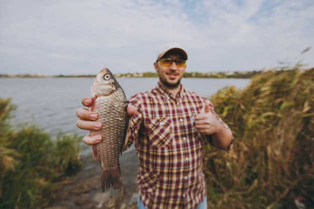 市松模様のシャツ、帽子、サングラスを身に着けた若い無精ひげを生やした男が魚を捕まえ、それを見せ、水と葦を背景に湖の岸で親指を立てます。ライフスタイル、レクリエーション、レジャーのコンセプト。