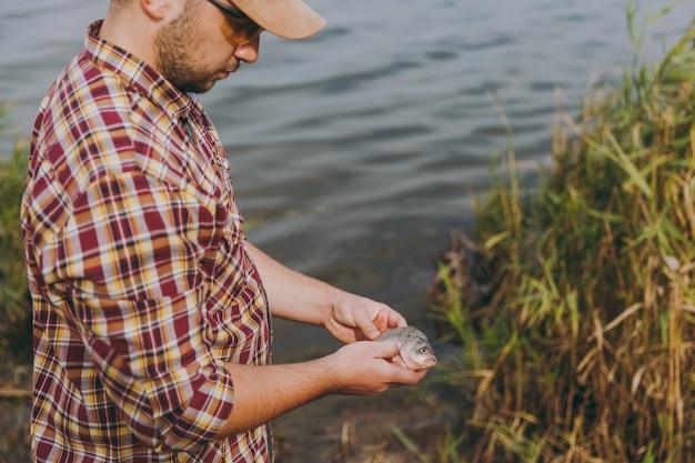바둑판 무늬 셔츠, 모자, 선글라스를 끼고 면도하지 않은 젊은 남자가 물고기를 잡고 물, 관목, 갈대 배경의 호수 기슭에서 팔에 안고 있습니다. 라이프 스타일, 어부의 레크리에이션, 레저 개념